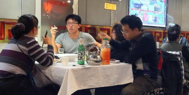 Smokers at tables flanking a no smoking sign in a Beijing restaurant.